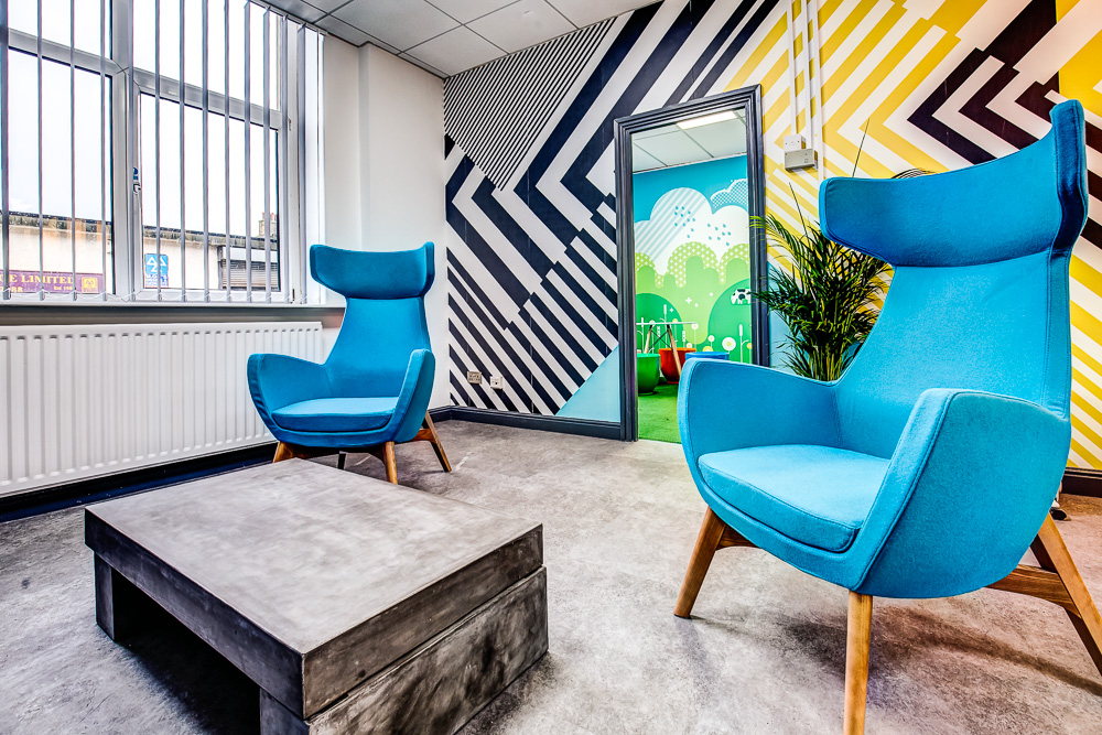 high back blue chairs in the middle of a room with bright wallpaper